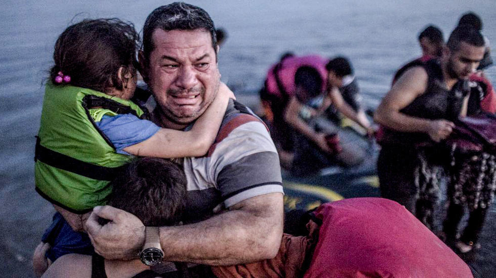 Man holds children as they exit escape boat