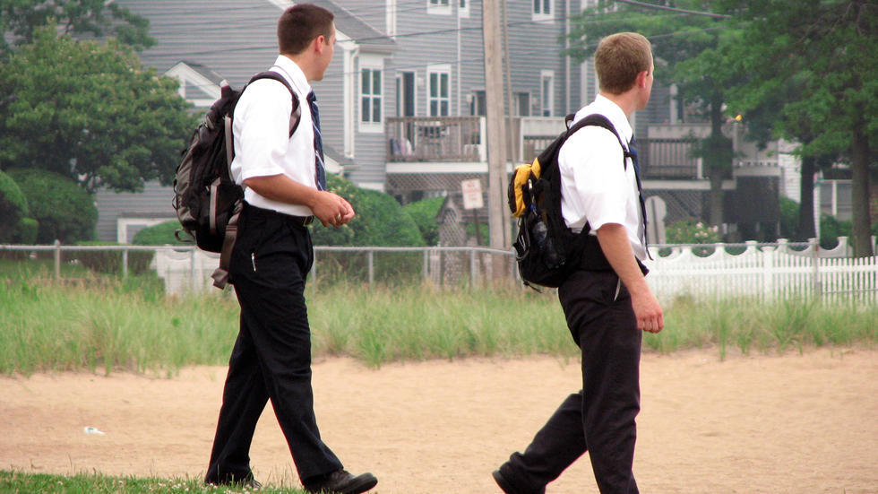 Mormon missionaries walking down the street in uniform.
