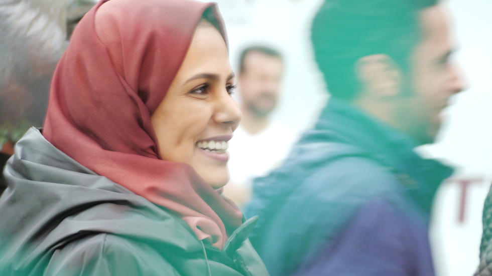 Woman in headscarf smiles at sports match