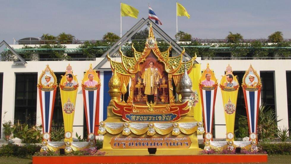 King Bhumibol standing on an ornate throne