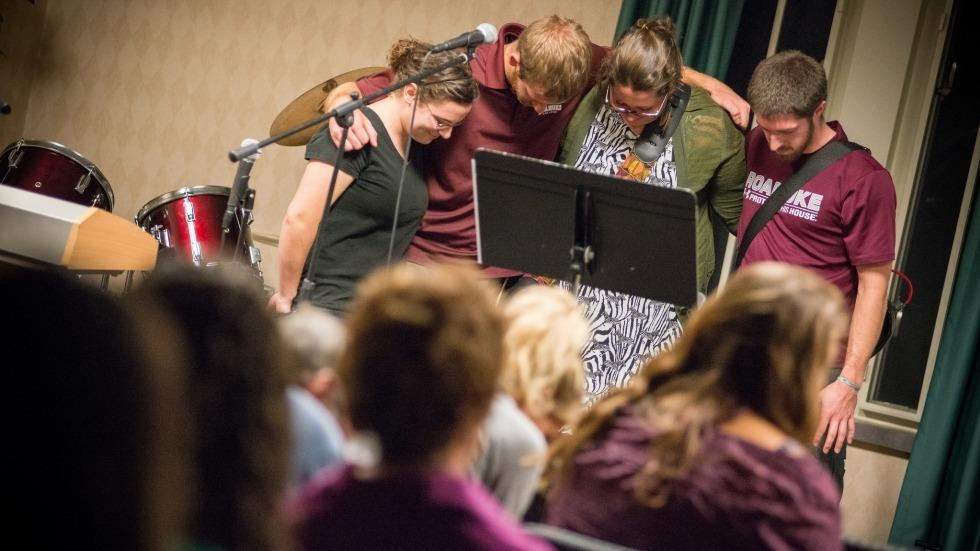 Students gather on stage at an InterVarsity meeting