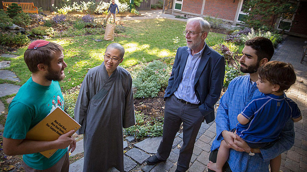 HDS student Daniel Kraft (from left), the Ven. Changshen Shi, CSWR Director Francis Clooney, Ph.D. candidate Seth Powell, and Powell's 2-year-old son, Ruben, talk in the center's courtyard.