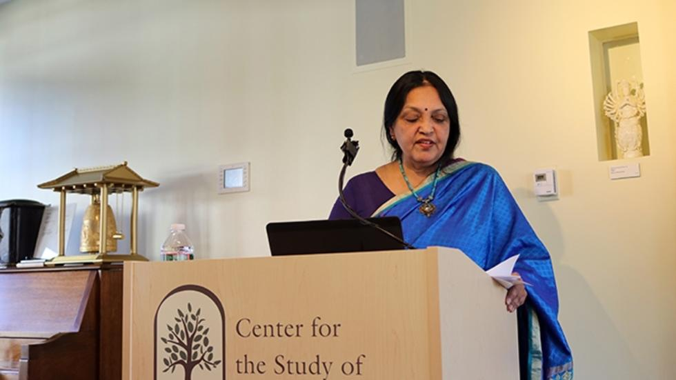 Picture of Vasudha Narayanan standing behind a podium
