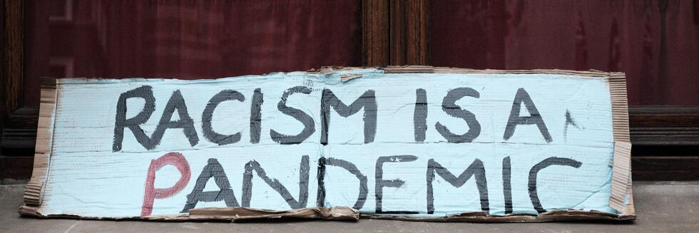 "painted cardboard sign reading ""racism is a pandemic"" in a window"