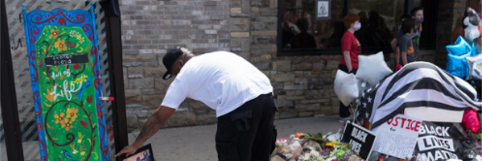 Image of a black person laying flowers at the site where George Floyd was murdered