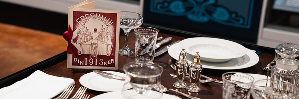 Menu with cutlery and plates on a table.