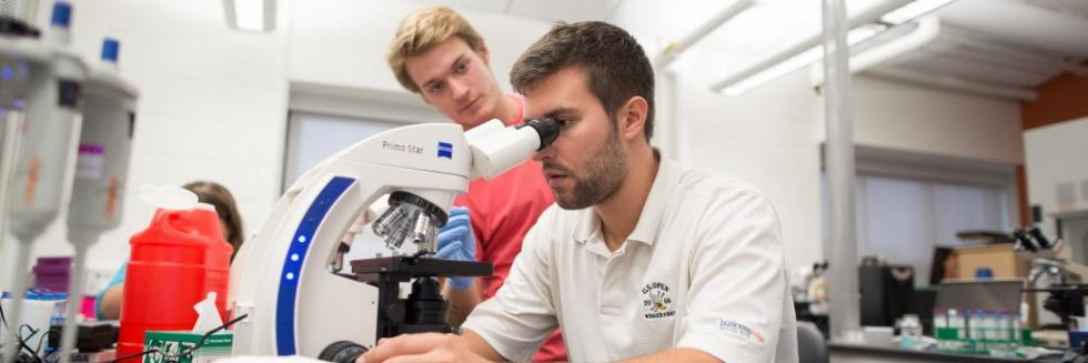 Male student sits at table looking into a microscope, another male student stands next to him