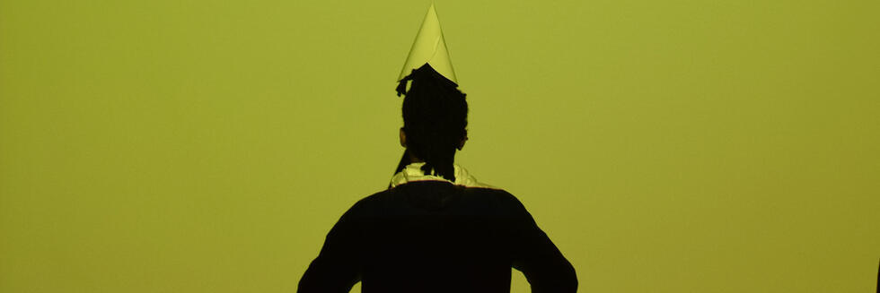 A man stands with a hat on against a projection of a yellow screen.
