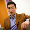A photo of David Liu sitting on a couch in his office