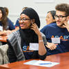 Two students sitting at a desk smile during a CUNY ASAP community session