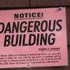 "A sign that reads ""dangerous building"" hangs outside a home in Chelsea Massachusetts"