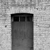 Boarded up door set within a worn brick wall