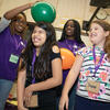 A photo of Nina Uzoigwe demonstrating static electricity with a balloon on the head of a young student while others look on