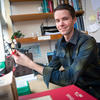 A photo of Porter Ladley holding a model of a molecule in his office space in the lab