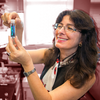 A photo of Joanna Aizenberg holding a vial of blue liquid