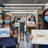 "A photo of lab members holding up signs that say ""First Day Back In Lab"""