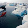 A double kayak with two people making their way through Arctic waters.