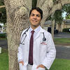 Gerardo Alvarez, DMD24, in his White Coat posing in front of a tree.