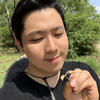 Sangil Kim holding an Anoplophora outdoors, trees in background