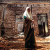 Sri Lankan Muslim woman looks at camera in scorched building