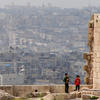 Two children stand on crumbling wall overlooking Aleppo