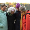 Sally Hammel (left), Laurie Sedwick, Angie Cecil and Gretchen Legler embrace following their sunrise pilgrimage to Walden Pond in November. Photo by Jeffrey Blackwell, Memorial Church