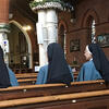 Four nuns seated in pews in a church. Photo by wikicommons