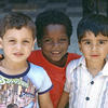 Three children in Akko draw together and smile for the photographer's camera.