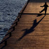 Person on dock in shadow by Boston Globe