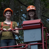 Molly and Jess riding in the bucket truck at the Harvard Forest