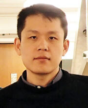 A headshot of Suyang Xu wearing a black sweater, looking directly at the camera