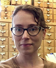photo of April Collins with a library card catalog in the background