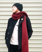 Man wearing an open black coat, white shirt, red scarf, black pants, and a black beanie, looking away from the camera.